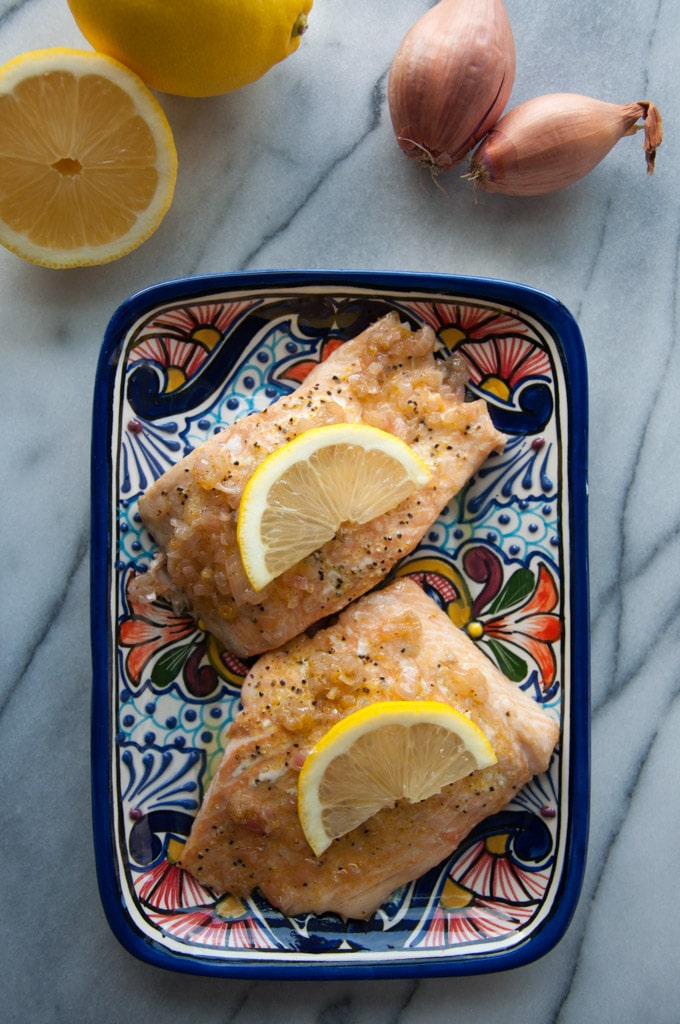two pieces of shallot lemon butter salmon on a plate beside a lemon and two shallots