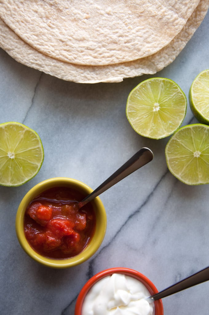 tortillas, limes, and a small bowl of salsa on a marble surface