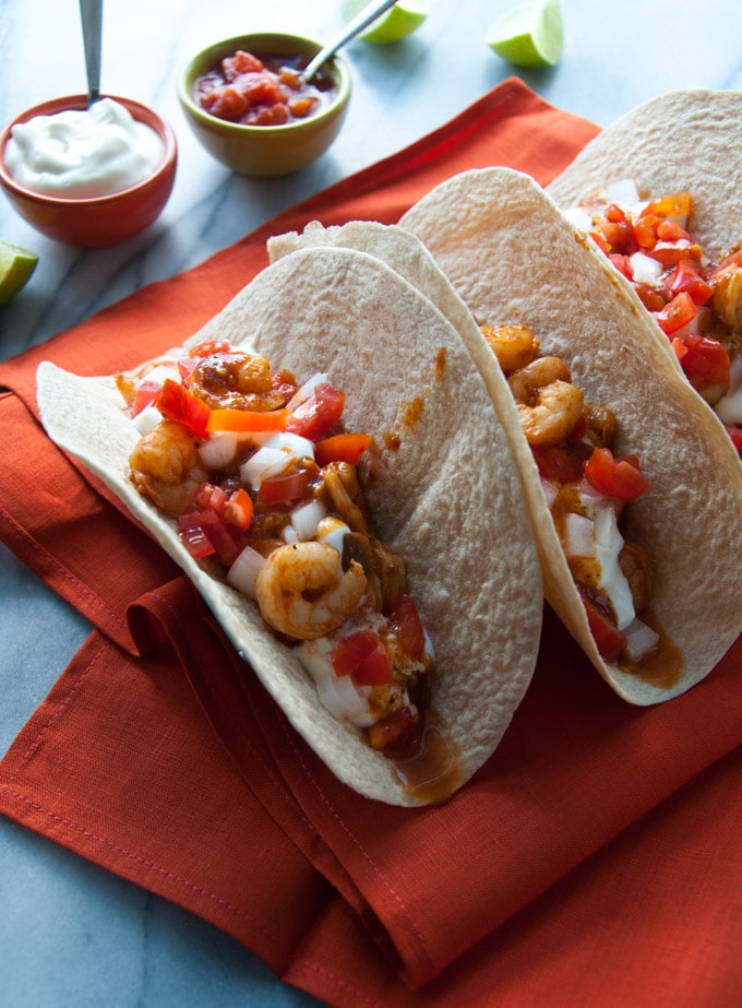 sweet and smoky BBQ shrimp tacos on a red cloth napkin