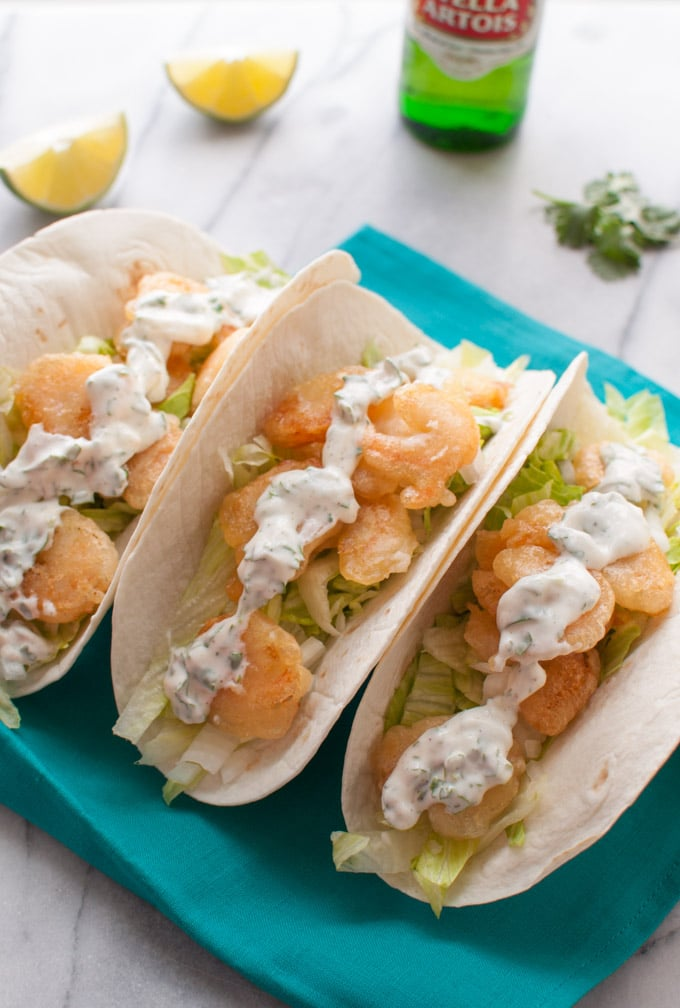 several beer battered shrimp tacos with cilantro lime cream