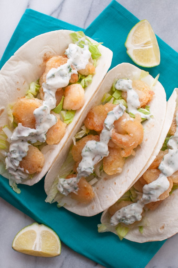 close-up of beer batter shrimp tacos with cilantro lime cream