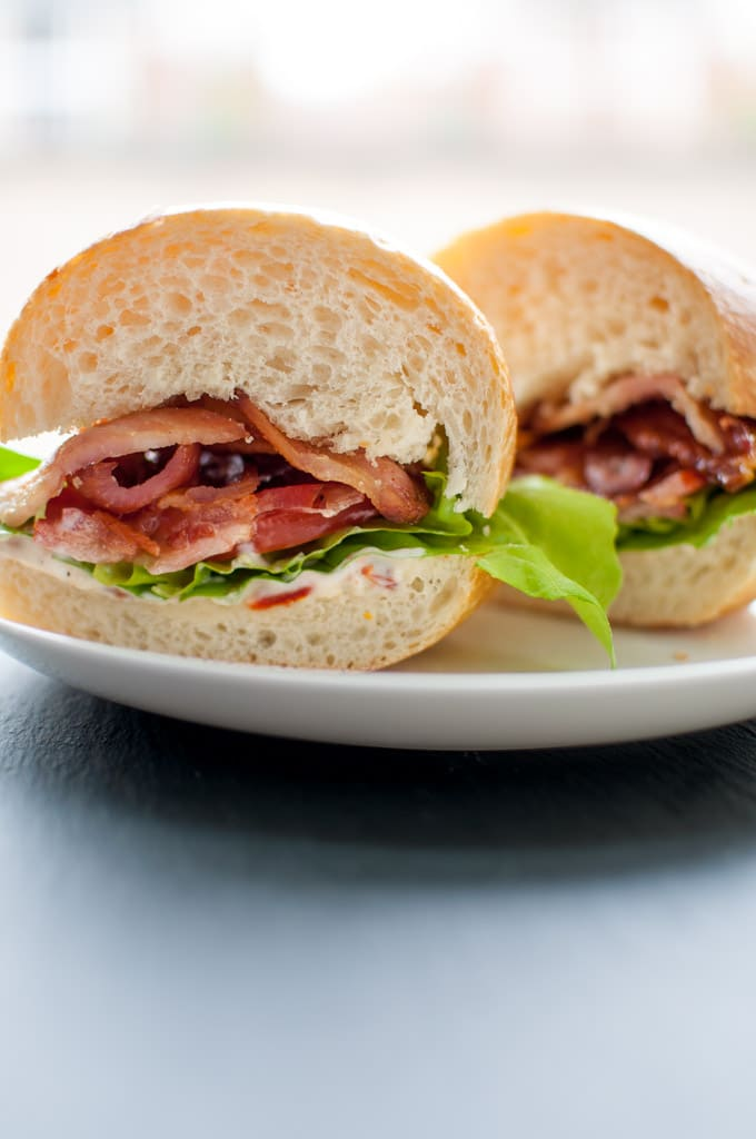 BLT with garlic and sun-dried tomato mayo cut in half on a plate