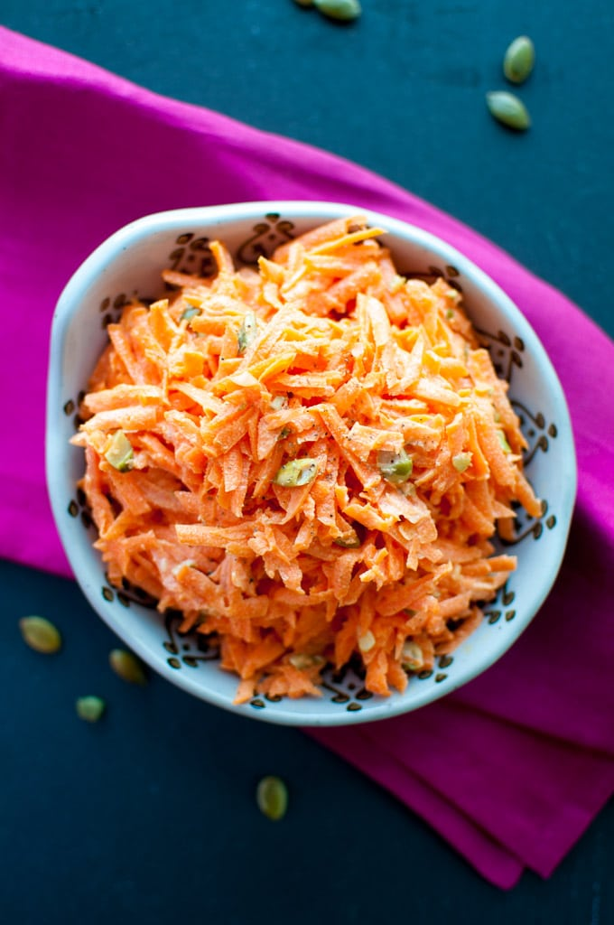 bowl with carrot salad with pumpkin seeds on a pink cloth napkin