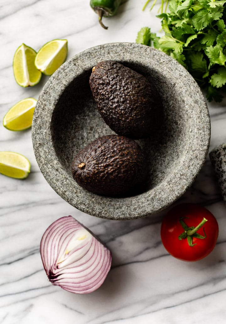 molcajete surrounded by guacamole ingredients ready to be prepped