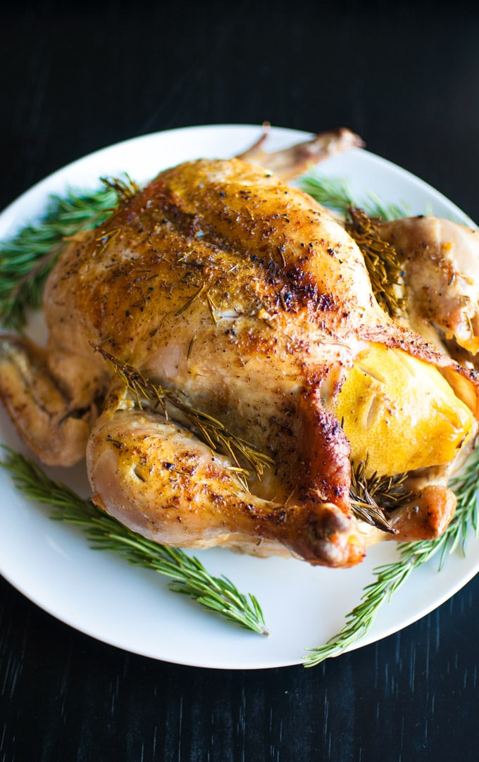 white serving plate with whole roasted chicken with lemon and rosemary sprigs