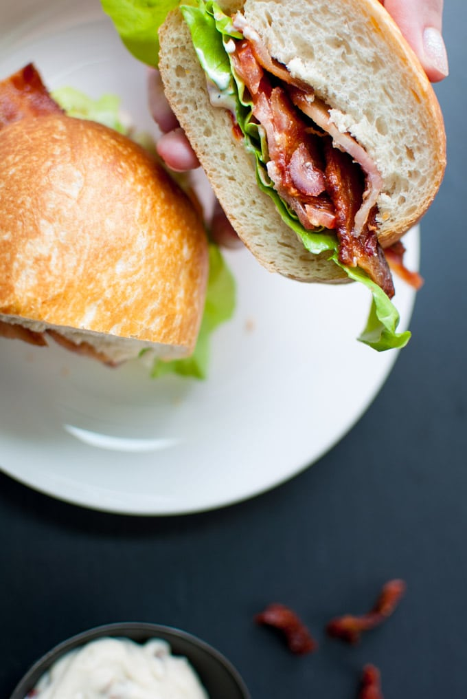 close-up of a hand holding half a BLT with garlic and sun-dried tomato mayo