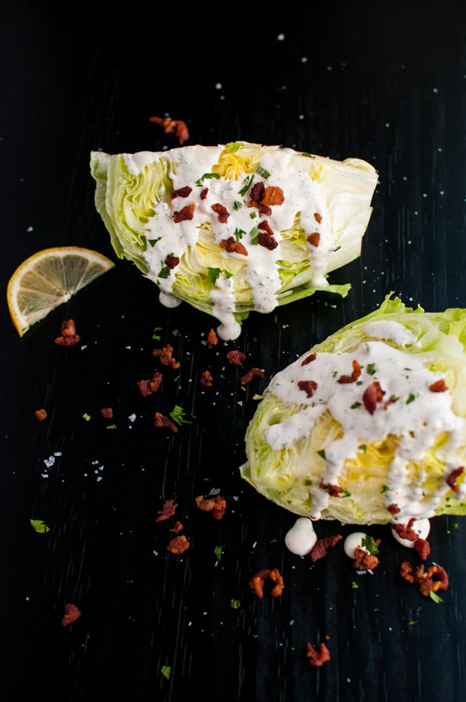 two iceberg lettuce wedges with ranch and bacon dressing and lemon slice