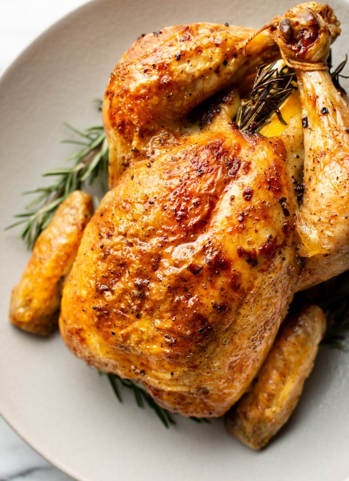 close-up of cooked crispy whole roast chicken in a shallow bowl surrounded by fresh rosemary