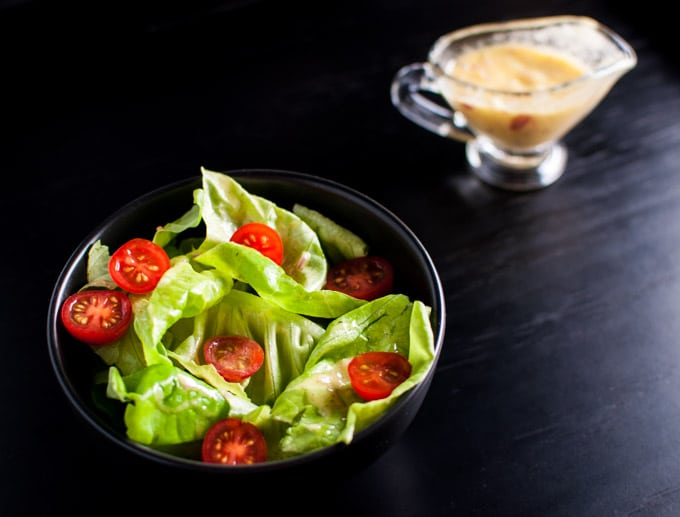 black salad bowl with iceberg lettuce, tomatoes, and the best vinaigrette
