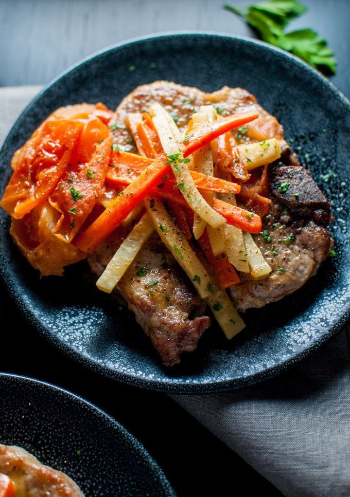 close-up of plate with pork chops with white wine, carrots, and celeriac