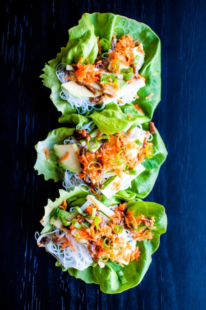 close-up of several vegetable lettuce wraps with a sweet peanut sauce