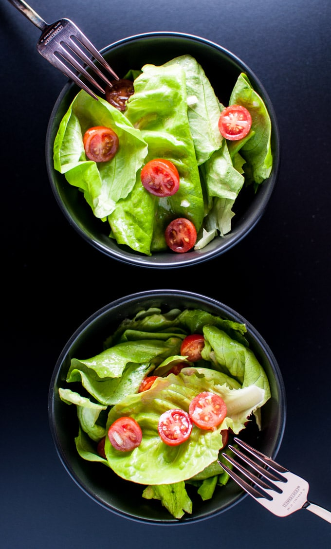 two bowls of salad with butter leaf lettuce, tomatoes, and the best vinaigrette