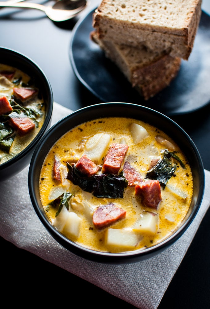 chorizo, white bean, and potato soup in a bowl with beside rye bread