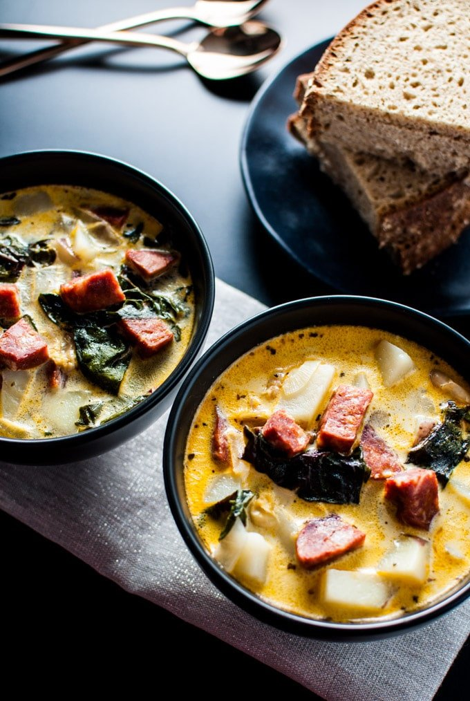 two bowls of chorizo, white bean, and potato soup with a stack of rye bread slices