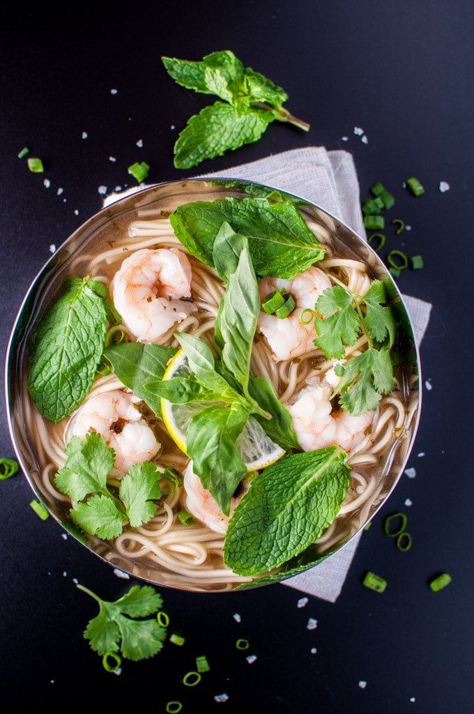 Asian-style shrimp and noodle soup in a metal bowl with mint and cilantro garnish