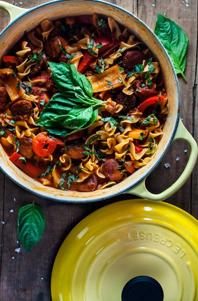 one-pot chorizo, bell pepper, and tomato noodles in a yellow pot with basil garnish