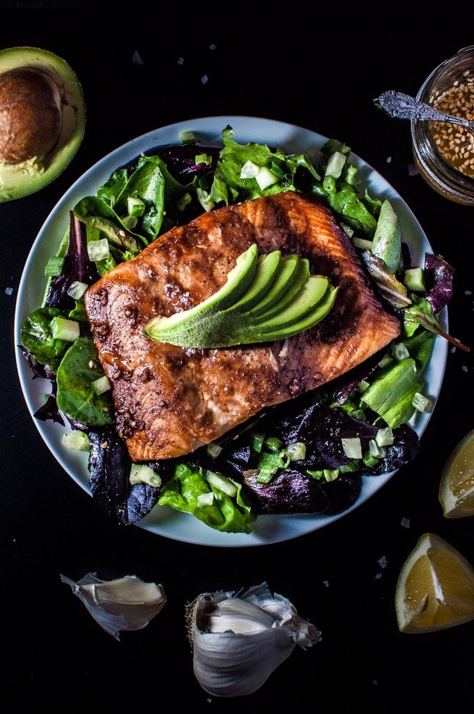 blue plate with salmon salad with spinach and a toasted sesame seed dressing topped with avocado slices