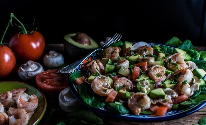 spinach salad with shrimp and a smoky sweet dressing on a table with extra ingredients and a fork