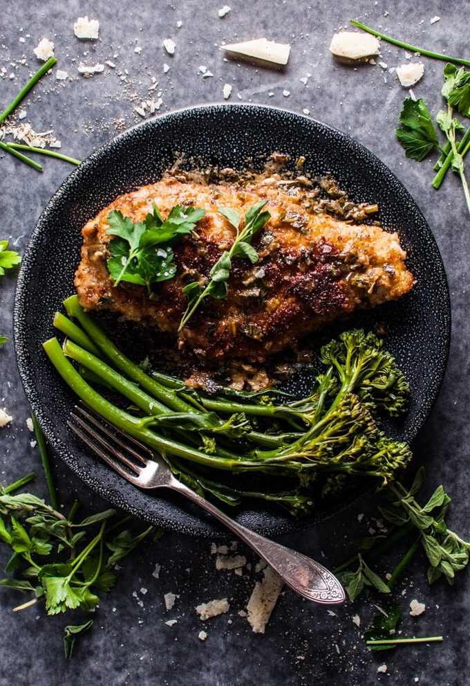 parmesan crusted chicken breast on a black plate with broccolini and a fork