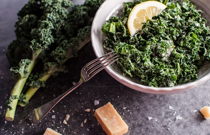 close-up of a bowl with kale salad with parmesan, lemon, and black truffle oil