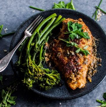 Parmesan crusted chicken breasts with a fresh herb sauce makes a wonderful weeknight meal. The parmesan breading keeps the chicken tender, while fresh chives, oregano, and parsley make the lemon butter sauce irresistible.