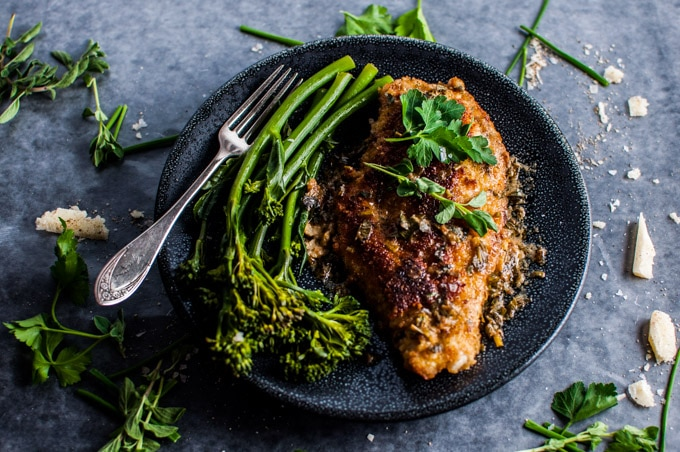 plate with parmesan chicken breasts with herb sauce on a plate with broccolini