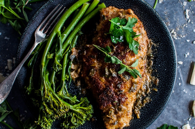 close-up of parmesan crusted chicken breasts with a fresh herb sauce