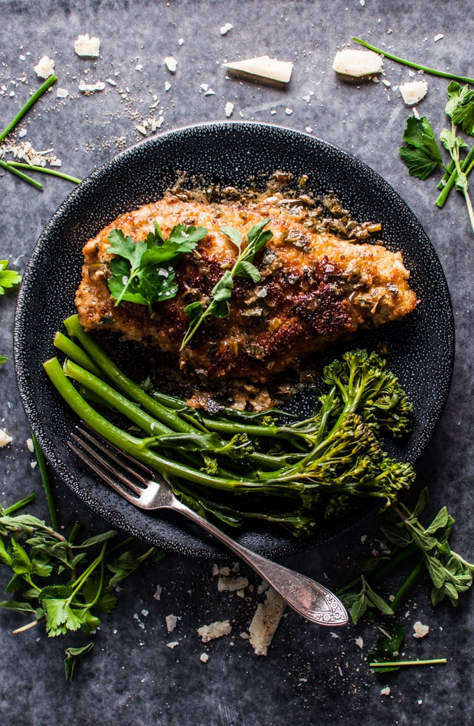 parmesan crusted chicken breasts with a fresh herb sauce on a plate with broccolini and a fork