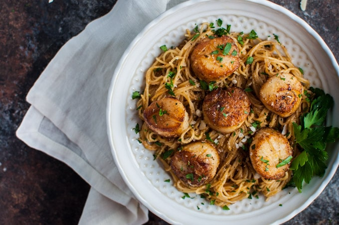 close-up of bowl with chipotle tarragon scallops with angel hair pasta