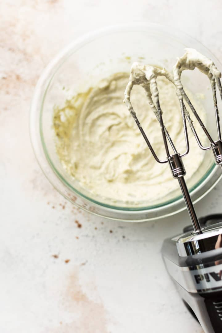garlic and herb spreadable butter in a glass prep bowl with electric hand mixer