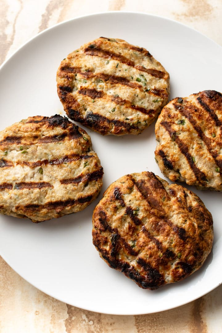 grilled ground chicken burger patties (cooked) on a plate