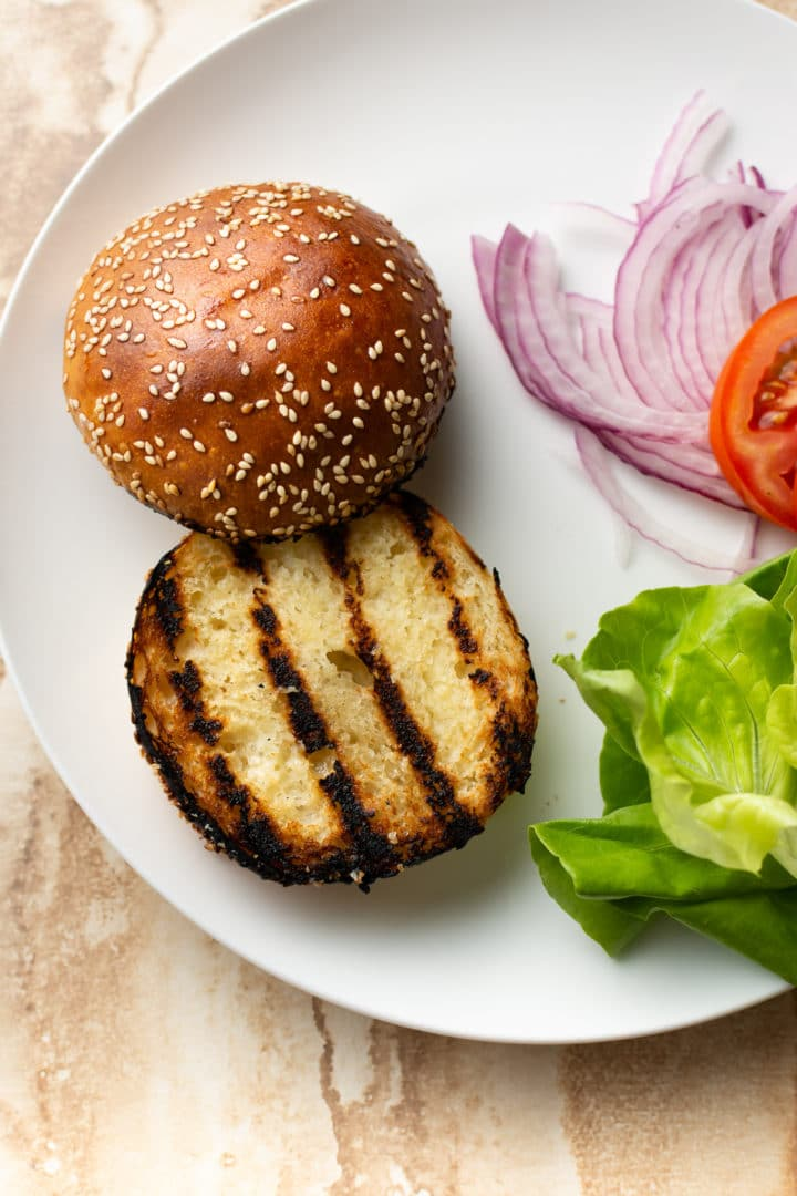 homemade ground chicken burger toppings on a plate (bun, lettuce, tomato, red onions)