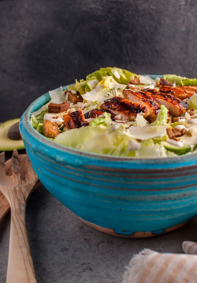 The ultimate summer salad: this caesar salad has tender and smoky BBQ chicken breast, garlic croutons, creamy avocado, oodles of shaved parmesan cheese, and a homemade lemony caesar dressing.
