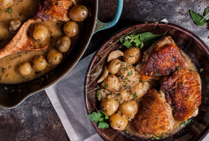 bowl of crispy lemon herb chicken and potatoes next to a skillet
