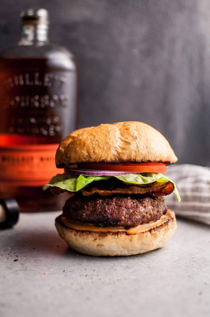BBQ bourbon burger with lettuce, tomato, and onion with a bottle of bourbon in the background