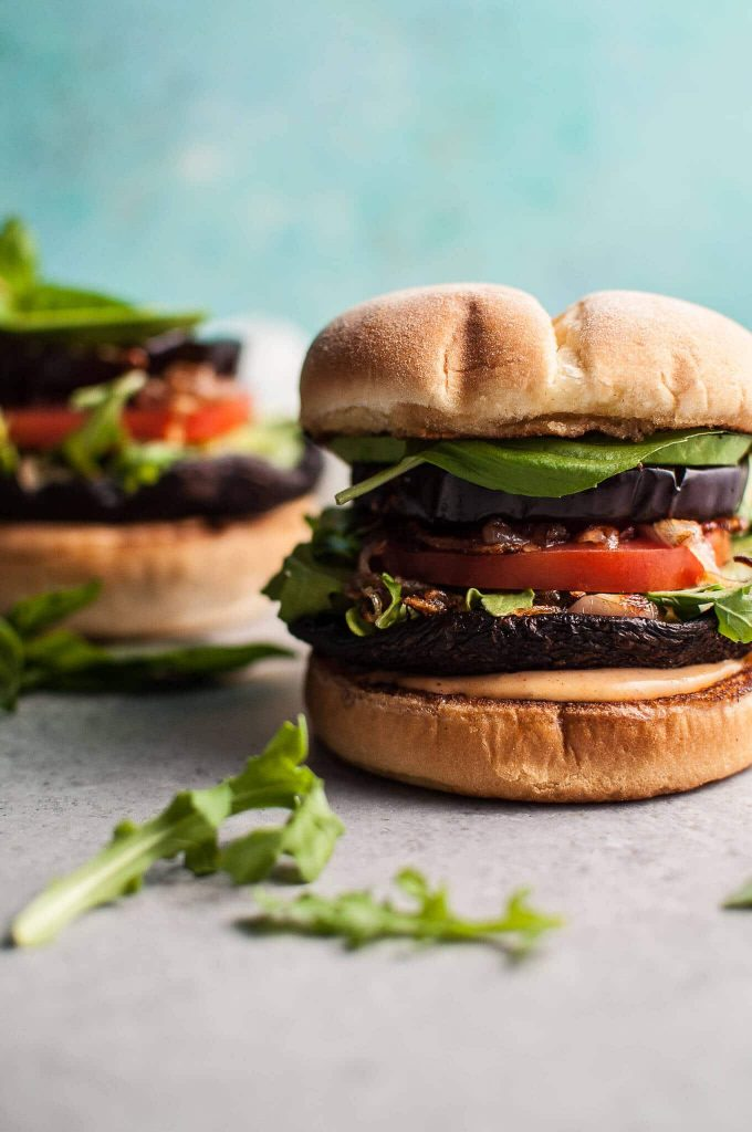close-up of a grilled portobello mushroom burger with eggplant and smoky mayo
