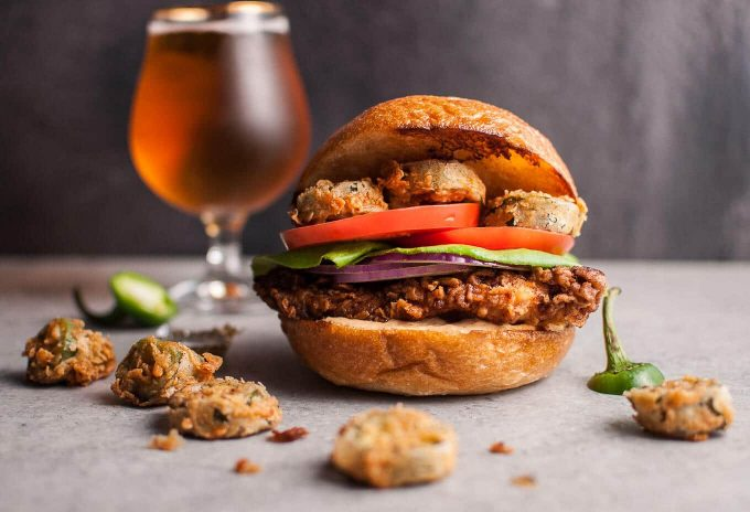 My Southwest fried chicken sandwich with fried jalapenos is a chicken sandwich dream come true. The chipotle cilantro lime ranch sauce packs a ton of flavor. The buttermilk fried chicken is crispy on the outside and tender and juicy on the inside. Fried jalapenos add the kick. Fresh tomato, lettuce, and red onion top it off.