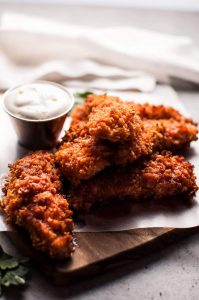 Sriracha honey chicken tenders are crunchy, spicy, sweet, and sticky. Served with a refreshing dipping sauce on the side!