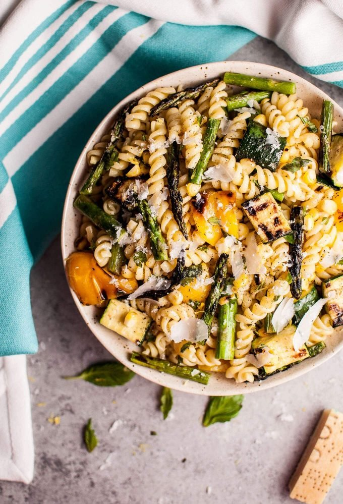 This grilled summer vegetable pasta salad is healthy and full of flavor! Zucchini, asparagus, corn, and yellow bell peppers are grilled to perfection and tossed with a fresh, lemony dressing. Easy to make and feeds a crowd!