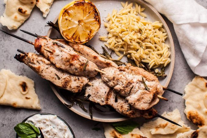 Juicy and flavorful rosemary chicken skewers are perfectly complemented with charred lemon and a delicious garlicky yogurt. Serve with orzo and naan, and you've got a fab feast on your hands.
