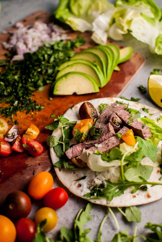 close-up of a summer steak taco with tomatoes and avocado slices