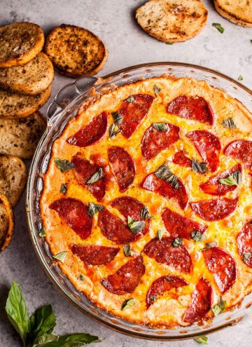 Chorizo pizza dip with garlic baguette slices for dipping... because all that cheese, garlic, and flavor just go so well together. This hot dip is easy to make and will please a hungry crowd!