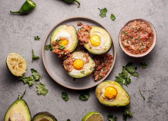 four huevos rancheros avocados on a plate next to dish of homemade salsa