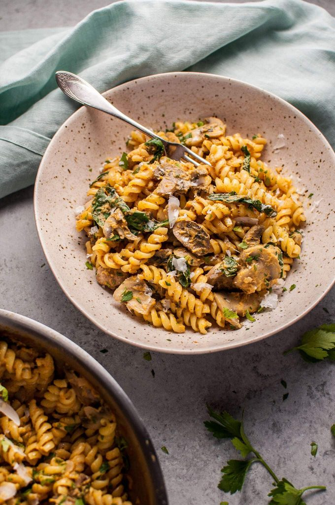 bowl of pumpkin, mushroom, and spinach pasta with a fork