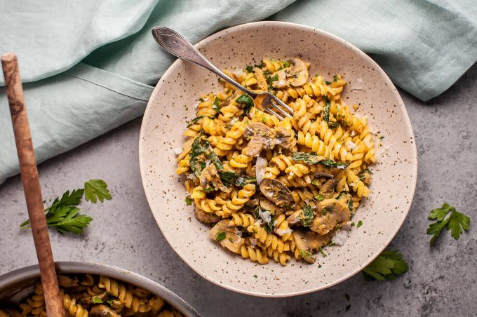 bowl of healthy pumpkin, mushroom, and spinach pasta with a fork