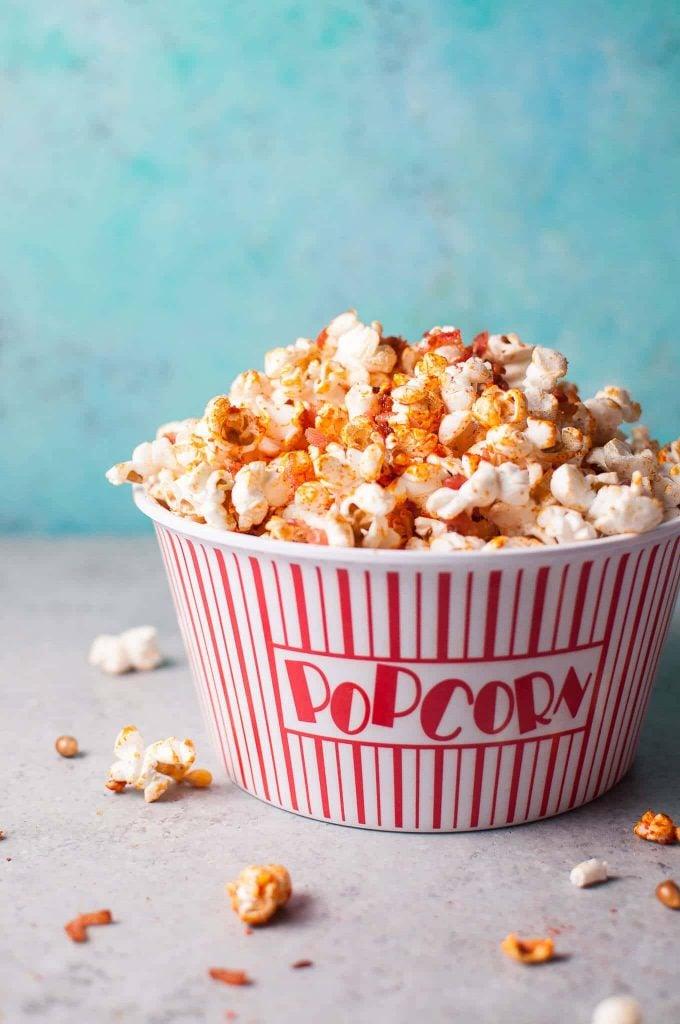 bowl of sriracha bacon popcorn on a blue background