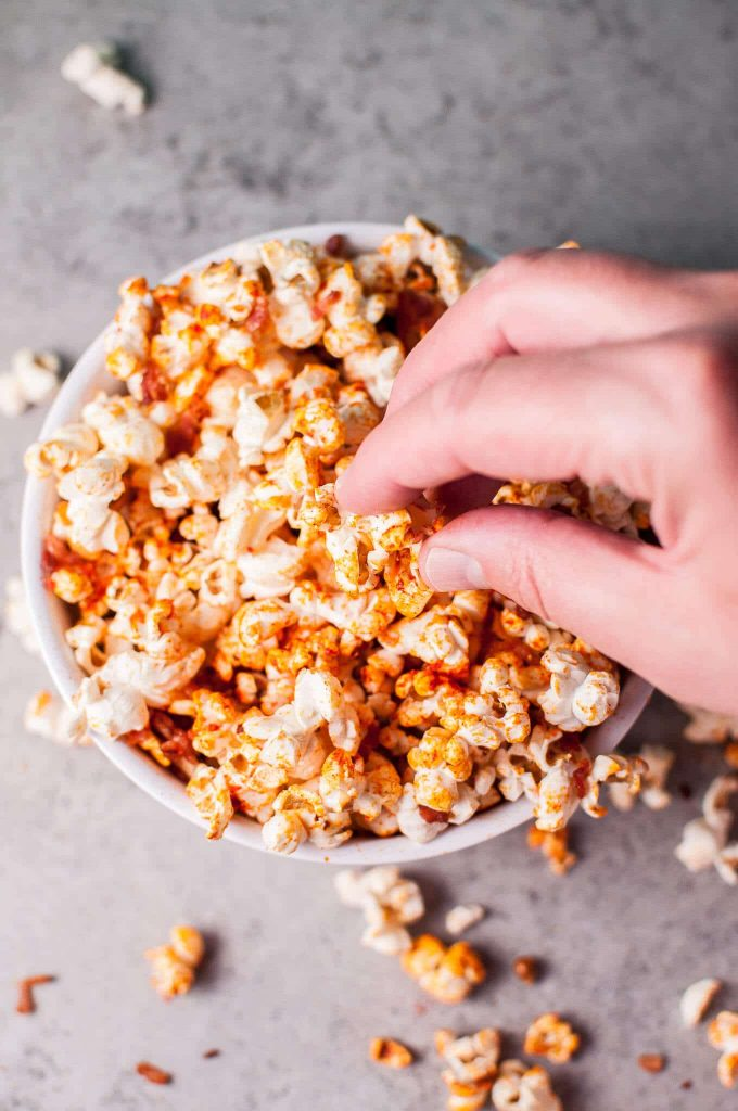 hand reaching into bowl of popcorn with sriracha and bacon seasoning