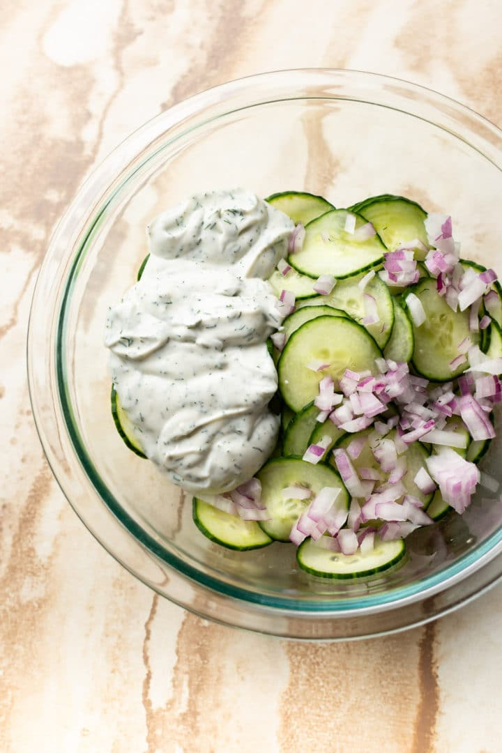 creamy cucumber onion salad in a glass prep bowl (not tossed yet)