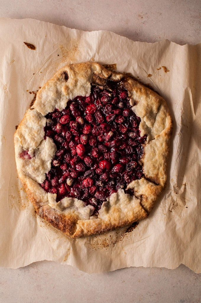 a whole festive cranberry galette on parchment paper