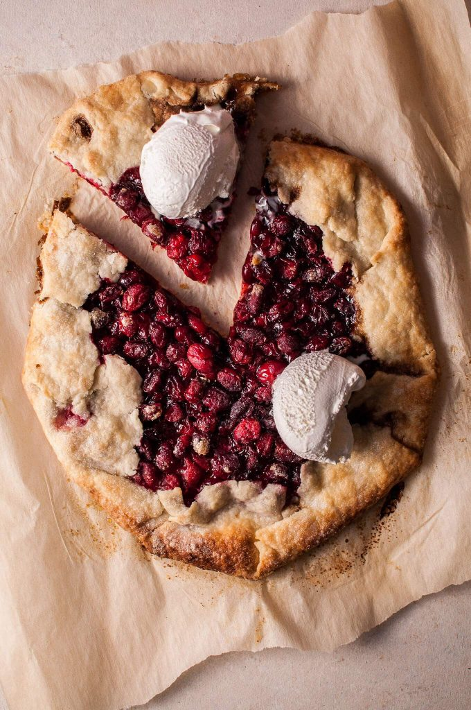 rustic cranberry galette on parchment paper with two scoops of ice cream